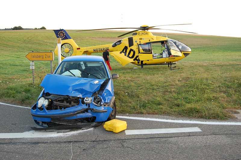 Eines der schwer beschädigten Unfallfahrzeuge vor dem Rettungshubschrauber