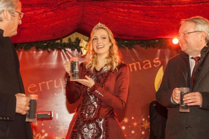 Die neue Glühweinprinzessin Laura Vogt bei der Präsentation des diesjährigen Glühweinglases mit Weihnachtspyramide (links Jochen Partsch, rechts André Schellenberg). (Foto: Darmstadt Marketing)