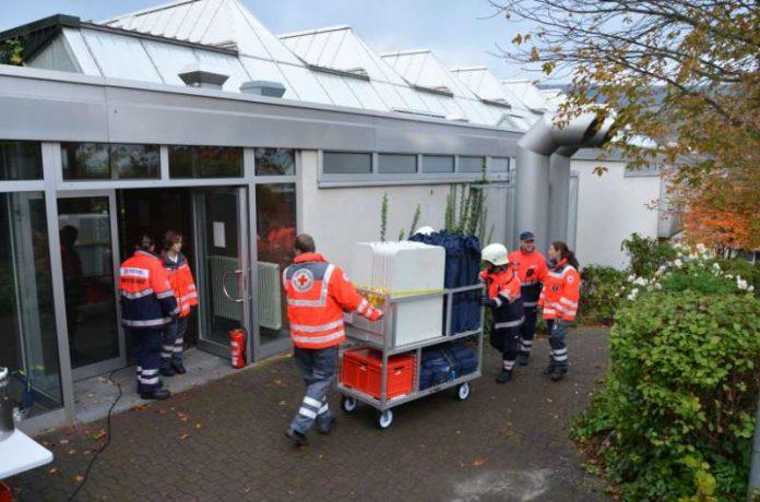 Helfer des Deutschen Roten Kreuzes und des Malteser Hilfsdienstes bringen bei der Katastrophenschutzübung Materialien für die Notfallunterbringung Evakuierter in die Turnhalle der BBS Bingen. (Foto: Kreisverwaltung Mainz-Bingen)