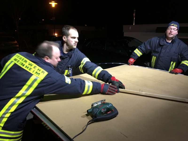 Die Feuerwehrangehörigen Marc Fath, Christopher Quintel und Dirk Baumann die eine Platte zuschneiden um eine Notverschalung in der Zinkgräfstraße durchzuführen. (Foto: Ralf Mittelbach)