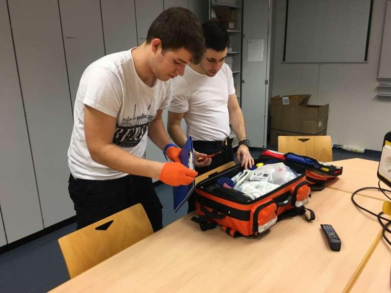 Die Feuerwehrsanitäter (v.l.) Johannes Ernst und Christian Paradiso, die nach einem Einsatz den Einsatzrucksack kontrollieren und wieder mit neuem Material bestücken. (Foto: Ralf Mittelbach)