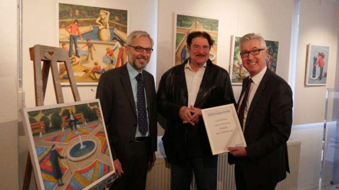 Prof. Dr. Matthias Maier (links) und Dr. Karl Roth (rechts) überreichen dem Künstler Benno Huth die Schenkungsurkunde. Im Hintergrund sind einige der Werke des Künstlers zu sehen. (Foto: Stadtwerke)