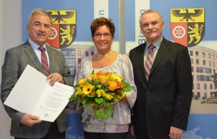 Landrat Claus Schick (links) und der Erste Kreisbeigeordnete Adam J. Schmitt (rechts) verabschieden Rosemarie Wenzel in den Ruhestand. (Foto: Kreisverwaltung Mainz-Bingen)