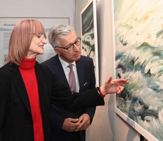 Künstlerin Brigitte Nowatzke-Kraft erläutert Dr. Karl Roth, Technischer Geschäftsführer der Stadtwerke, eines ihrer Gemälde. (Foto: ARTIS - Uli Deck)