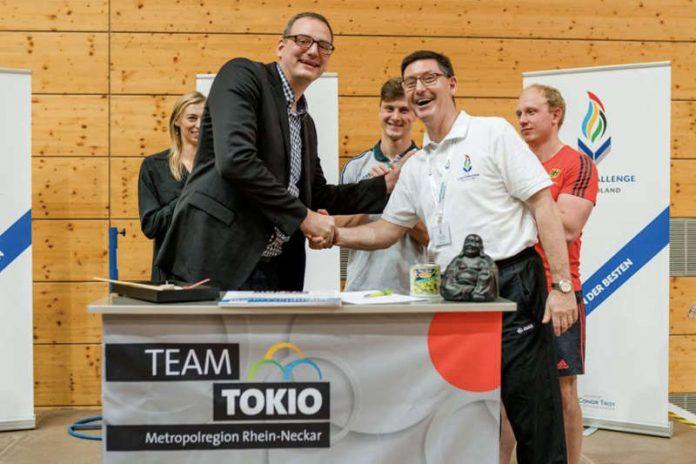 OSP Leiter Daniel Strigel (links) und Conor Troy (rechts) besiegeln die Zusammenarbeit. Im Hintergrund Stabhochspringerin Lisa Ryzih und die beiden Rugby-Nationalspieler Niko Müller und Phil Szezegin (Foto: Tobias Dittmer)