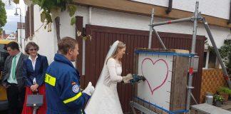 Die Braut schneidet das Herz mit der Säbelsäge aus, nachdem ihr Bräutigam (in THW-Jacke) zuvor das Eisengitter entfernte (Foto: THW)