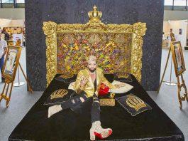 HARALD GLÖÖCKLER auf einem Boxspringbett-Unikat von Femira mit einem Kopfteil wie ein Gemälde. Das von ihm selbst gestaltete Bett feiert auf der EUNIQUE eine exklusive Preview. (Foto: KMK / Jürgen Rösner)