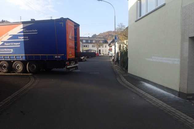 Heck des LKW mit Schaden am Haus