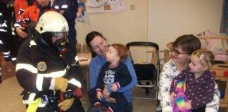 Feuerwehrmann Dennis Stark zeigt Castiel (li.) und Leonie (re.) die Bedienung eines Hohlstrahlrohres in voller Schutzausrüstung (Foto: Feuerwehr Bad Kreuznach)