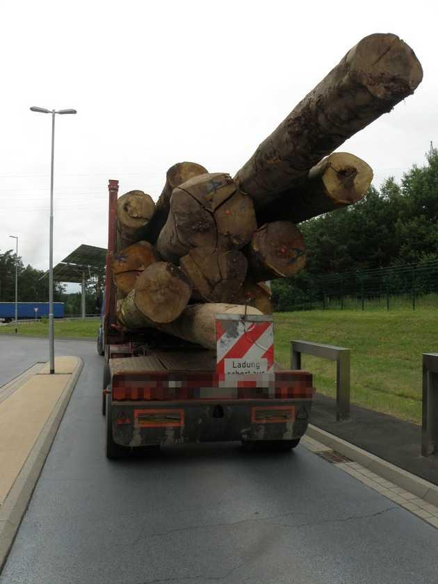 Völlig überladener Holztransporter