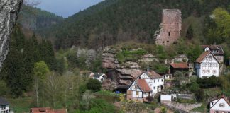 Blick vom Rehfelsen zur Burgruine Elmstein, links unten sieht man die Dächer der Mühle und Wappenschmiede, ein früheres Mühlenensemble mit ehemals fünf Wasserrädern an einem vom Speyerbach abgezweigten Kanal. (Bild: Benno Münch)