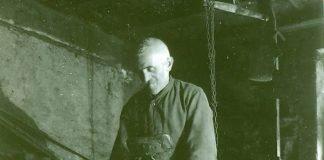 Hammerschmied Daniel Haag beim Schärfen eines Werkzeugs am großen Schleifstein um 1928 (Bild: Archiv Wappenschmiede)