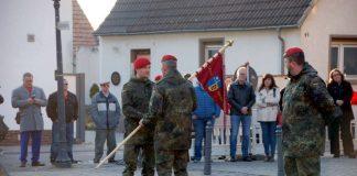 """Der Bataillonskommandeur (mitte) bei der Übergabe des Kompaniewimpels von dem alten (rechts) an den neuen Kompaniechef (links). / Oberleutnant Peter Gräfe (Foto: ABCAbwBtl 750 """"BADEN"""" – Walderstein)"""