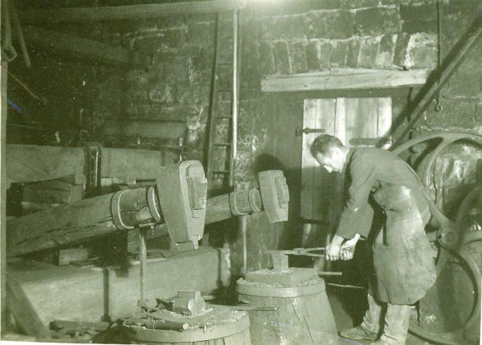 Historisches Foto )Ende der 20er Jahre): der letzte Hammerschmied Heinrich Haag am Amboss (Archiv Förderverein, Gemeinde, Siebein).