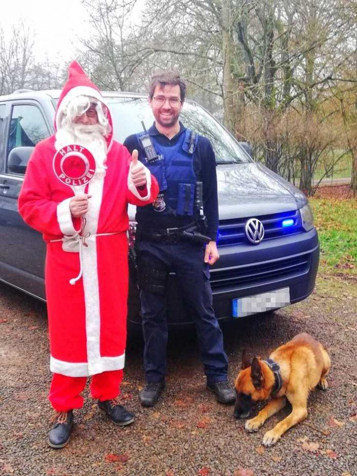 Weihnachtsmann und Polizeihundeführer mit Diensthund Dzuba