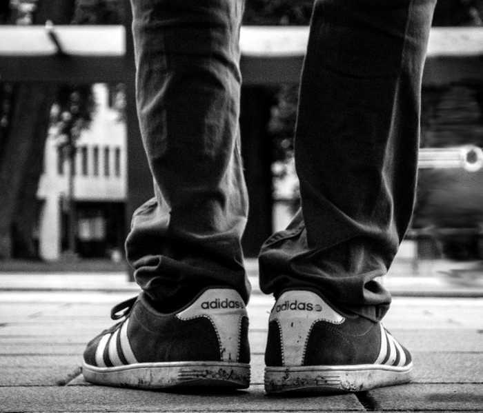 Symbolbild, warten, stehen, Turnschuhe, Beine, Hose, schwarz-weiss (pxhere)
