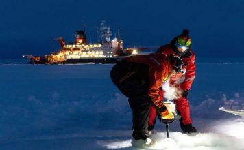 Zwei Forscher arbeiten auf dem Meereis. Im Hintergrund liegt die POLARSTERN. (Foto: Marcel Nicolaus, Alfred-Wegener-Institut)