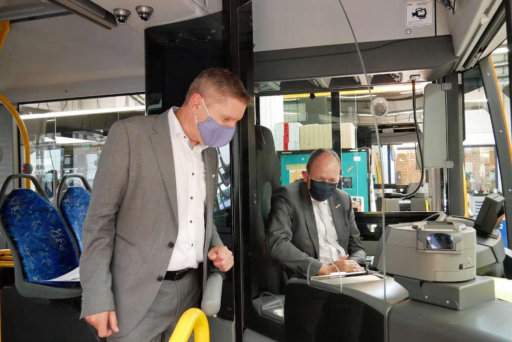 Martin in der Beek, Technischer Geschäftsführer der rnv, und Christian Specht, Aufsichtsratsvorsitzender der rnv, in einem Bus, in dem eine neue Glastrennscheibe verbaut wurde. (Foto: rnv GmbH)