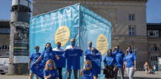 """Der blaue Riesenwürfel am Willy-Brandt-Platz vor dem Mannheimer Hauptbahnhof fällt auf! Drei soziale Einrichtungen, der Zentrale Lehrgarten Mannheim und das TECHNOSEUM in Mannheim werben gemeinsam mit Oberbürgermeister Dr. Peter Kurz und Kirsten Korte, Geschäftsführerin, Zukunft Metropolregion Rhein-Neckar e.V. bei einem Fototermin rund um den Würfel für ein Engagement beim Freiwilligentag der Metropolregion Rhein-Neckar, der unter dem Motto """"Wir schaffen was!"""" am Samstag den 19.09.2020 stattfindet. (Foto: MRN GmbH/Go7)"""