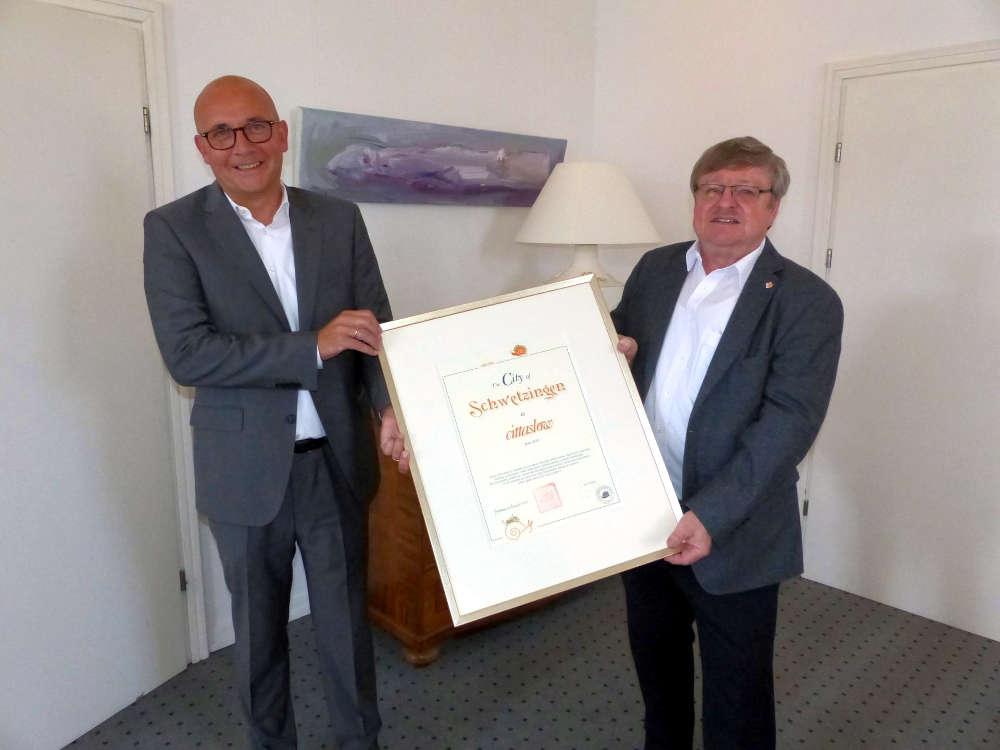 Manfred Dörr (rechts) überreicht seinem Amtskollegen Dr. René Pöltl die offizielle Urkunde (Foto: Stadtverwaltung Schwetzingen)