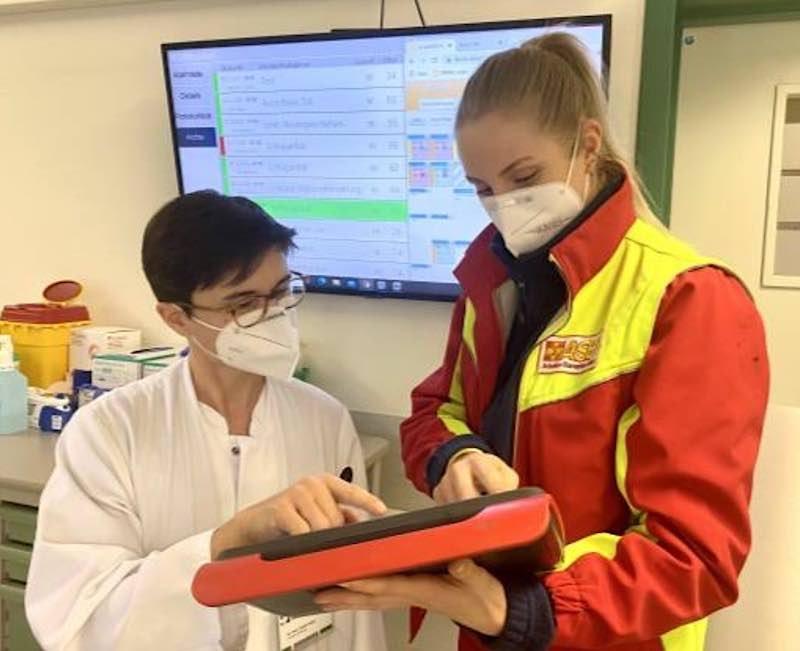 Patientenübergabe von Anna Maria Würmell (ASB) an Dr. med. Carolin Hoyer, Neurologin der Zentralen Notaufnahme, vor dem Arrival Board. (Foto: UMM)