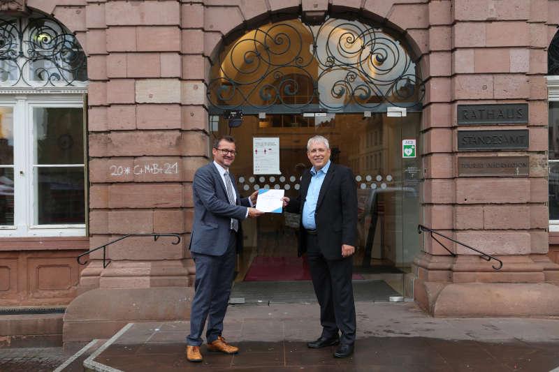 Volker Schütze übergab die Ernennungsurkunde vor dem Rathaus an Bürgermeister Raoul Schmidt-Lamontain (links). (Foto: Stadt Heidelberg)